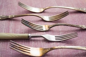 Set of old forks on a dirty pink background, selective focus