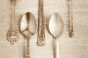 Old teaspoons on vintage  background. Monochromatic photo