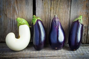 Eggplant fresh from the garden, lined up in a row on the wooden