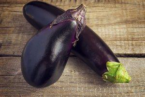 Two eggplant on an old wooden table