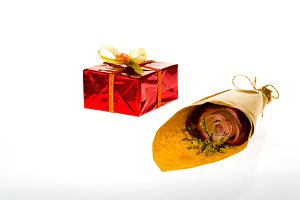 Bouquet of flowers in parchment paper and wrapped gift on a white background