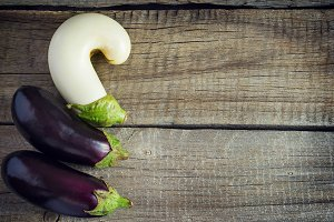 Three eggplants on an old wooden table, Copy space background