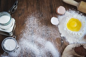Baking  vintage background with raw egg, flour, sugar and cocoa
