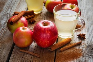 Apples, cider and cinnamon on old wooden table