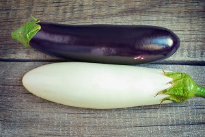 White and purple eggplant on old wooden background