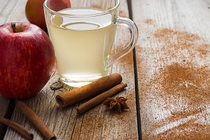 Fresh juicy apple, apple drink in a cup and cinnamon sticks.