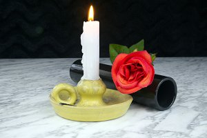 Red roses with black vase and candle