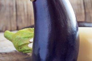 Big purple eggplant on wooden background, still life