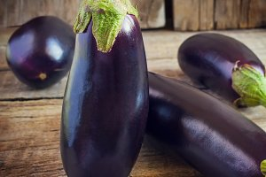 Composition of dark blue eggplant on old wooden table