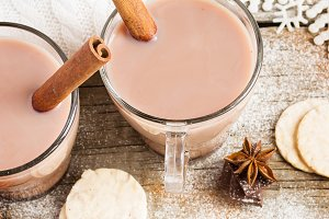 Cocoa with cinnamon on wooden background. Snowing.