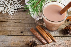 A cup of cocoa with cinnamon on a wooden background.