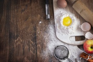 Baking background with raw egg, flour and apple, empty template