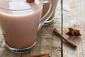 Hot cocoa in a cup with cinnamon on a wooden background