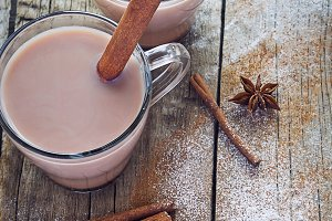 Two cups of hot cocoa with cinnamon on a wooden background