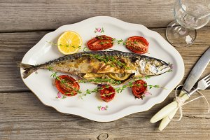 Baked mackerel with tomato and lemon in a vintage plate