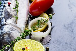 Fresh raw mackerel with tomato and lemon on a black metal pan