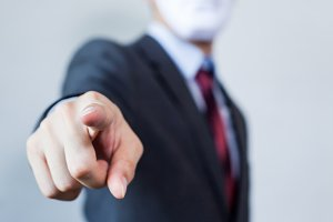 Man in white mask in business suit pointing fingers at