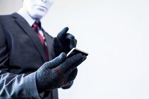 Business man in white mask wearing gloves and using mobile phone - fraud, hacker, theft, cyber crime concept