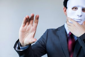 Anonymous businessman in mask hiding himself having holding something gesture - with copyspace