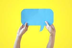 Human Hands Holding Blue Speech Bubble Over Yellow Background - Balloon speech bubble concept