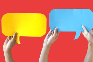 Human Hands Holding Yellow, Blue and White Speech Bubbles Over Light Orange Red Background - Fun Balloon speech bubble concept