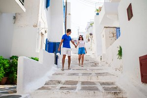Family vacation in Europe. Happy couple at street of typical greek traditional village on Mykonos Island, in Greece