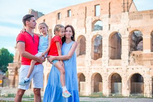 Happy family in Rome over Colosseo background. Italian european vacation together