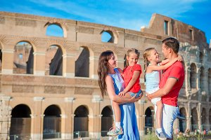 Happy family in Europe. Parents and kids in Rome over Coliseum background. Italian european vacation together