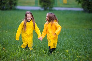 Adorable little girls under the rain on warm autumn day