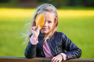 Portrait of adorable little girl with yellow leaves outdoors at beautiful autumn day