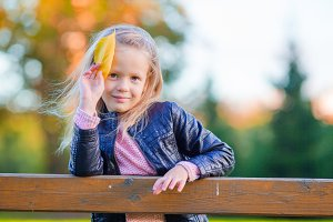 Portrait of adorable little girl with yellow leaf outdoors at beautiful autumn day