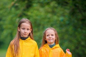 Adorable little girls under the rain on warm autumn day