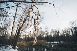 Dreamcatcher against a white blur of snow. Outdoor moody photography of winter forest landscape in faded colors.