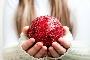 Red christmas ball in hands
