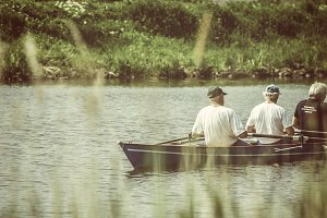 Three gray haired men rowing