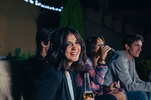 Woman holding beer and her friends talking in a party