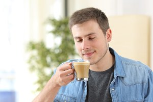 Man tasting coffee with milk