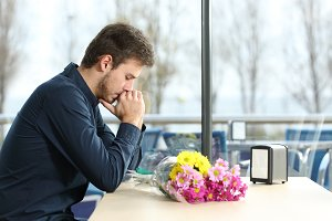 Sad man with bunch of flowers