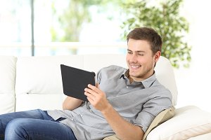 Happy man using a tablet on line