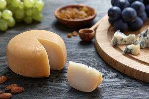 Round cheese with grapes on wooden backround