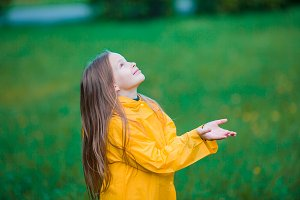 Little girl enjoy the rain on warm autumn day