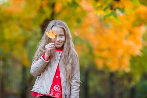 Amazing little girl outdoors at beautiful warm day in autumn park with yellow leaf in fall