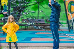 Little girl enjoy rainy weather in outdoor playground, while dad is suprised