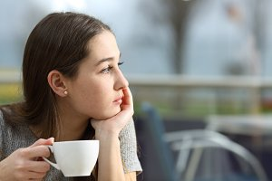 Pensive woman holding a coffee cup