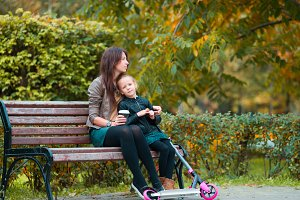 Adorable little girl with mom enjoy fall day in autumn park outdoors