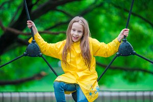 Happy little girl playng on outdoor playground