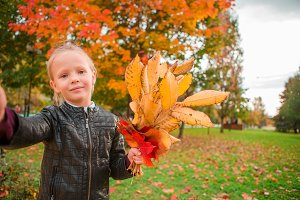 Adorable little girl taking selfie portrait with yellow and orange leaves bouquet outdoors at beautiful autumn day