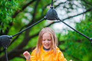 Little girl enjoy rainy weather in outdoor playground have fun with dad