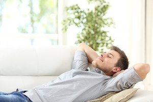 Relaxed man resting lying on a couch