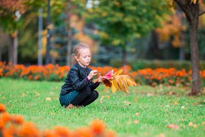 Little girl with yellow leaves bouquet outdoors at beautiful autumn day in fall